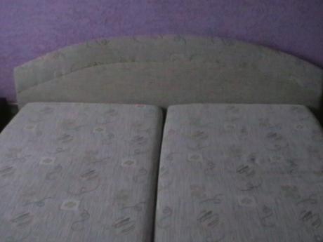 manželská posteľ s roštom v sivom prevedení,