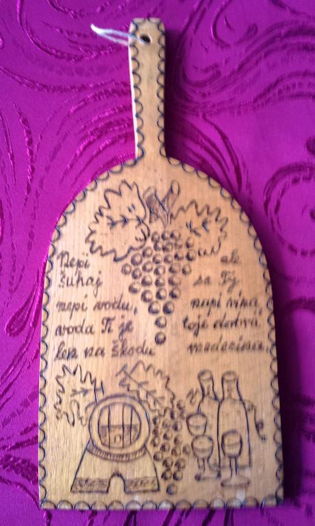 ozdobný drevený lopár a hlinený maľovaný tanier,
