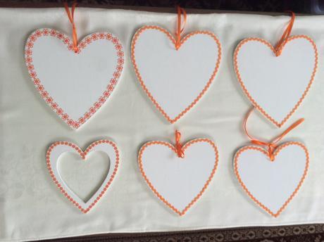 6 bílých dřevěných srdcí s oranžovým zdobením,