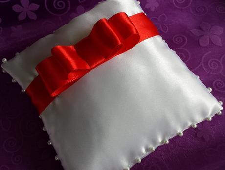 Bílý polštářek pod prstýnky s červenou mašličkou,