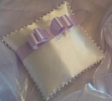 Bílý polštářek pod prstýnky s lila mašličkou,