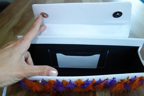 Bílá kabelka s oranžovo-fialovými pírky,