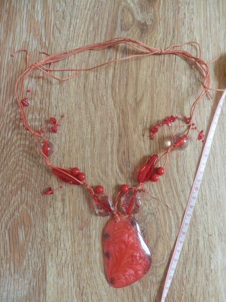 Výrazný červený náhrdelník s velkým přívěskem.,