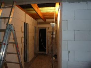 Pohlad z obyvacky ku vchodovym dveram. Prave manzel robi poklop (dreveny strop)