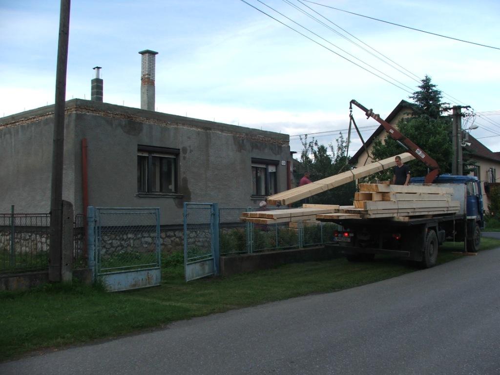 Dom so žltými dverami - drevo na nový krov