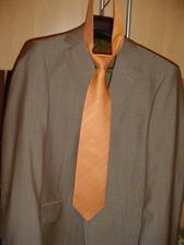 Ženichův oblek i s kravatou. Ještě do toho přijde stejně oranžová košile