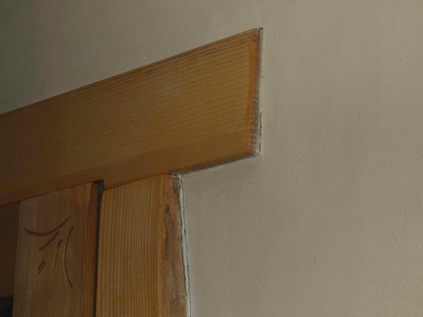 Hlinené omietky a podlahy svojpomocne. - Detail priomietnutia zárubne s priznanou hranou. Íl pri vysychaní vytvára na spoji s drevom dilatačnú škáru.