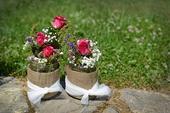 Vázy s bílou stuhou a jutou se sušenými květinami,