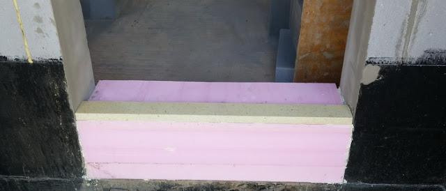 Raciodom - Z dôvodu nežiadúcich tepelných mostov sa vchodové a terasové dvere osadili na XPS (zlepený z viacerých častí pomocou lepidla na EPS). Na vrch sa osadila konštrukčná doska Phonotherm