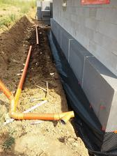 Po zateplení základov sa na EPS osadila nopová fólia, ktorá ochráni EPS pred mechanickým poškodením a taktiež bude slúžiť ako ochrana EPS proti vode. Vedľa je pripravené kanalizačné potrubie pre odvod dažďovej vody.