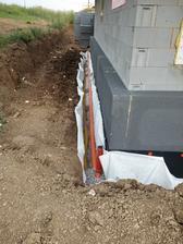 V hornej časti domu sa do výkopu osadila geotextília, ktorá zabráni prechádzaniu nečistôt do drenážnej vrstvy. Na najnižšie miesto sa uložila drenážna rúra fi 100 mm. Do výkopu sa taktiež vložila kanalizačná rúra fi 100 mm