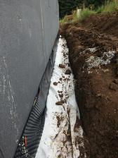 Drenážna vrstva pozostavajúca z makadamu a drenážnej rúry sa následne uzavrela geotextíliou a zasypala zeminou.