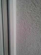 Napojenie fasády na rám okna pomocou APU lišty, ktorú v podstate ani nie je vidieť. Taktiež detail na Štruktúru a farbu fasádnej omietky.