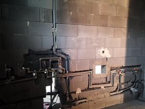Pohľad do kúpelňe. Osadená aj podomietková termostatická batéria. Na utesňovanie skrutkovacích spojov sa používalo konopné tesnenie, ktoré sa natrelo ľanovou fermežou a spoj sa opatrne dotiahol.  Takýto spoj sa stane za niekoľko rokov nerozoberateľný