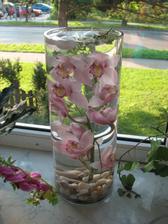 veľká dekoračná váza s orchideami a plávajúcimi sviečkami