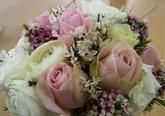 Kytice je složena z růží, eustomy, waxu