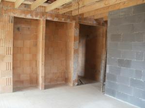 Obývačka - krb, vedľa priestor na drevo a chodba