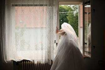 Nevěsta šmíruje svatebčany oknem