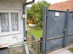 Pohľad do dvora so studňou cez skulinku popri bráne.
