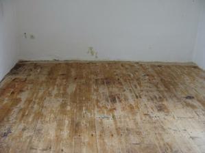 Po odtránení dvoch vrstiev gumolitu sme objavili zachovalú drevenú podlahu - žial v miestach, kde stál ťažký nábytok bez nožičiek bolo drevo spráchnivené