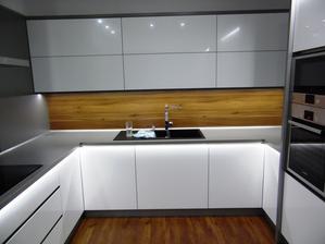 Vysoký bílý lesk stříkaný na čelních plochách,kombinovaný s ořechem evropským.Deska titan a osvětlení LED studená.