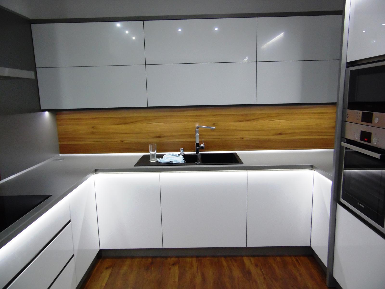 Kuchyňské linky....realizace - Vysoký bílý lesk stříkaný na čelních plochách,kombinovaný s ořechem evropským.Deska titan a osvětlení LED studená.
