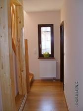 Část spodní chodby - pohled z kuchyně, naprova dveře do pracovny, nalevo schody a fachwerk (dřevěné nosníky)