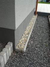 Násyp skaliek okolo domu aj okolo terasy.