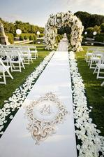 ..béžový koberec s bílo-růžovými lístky...