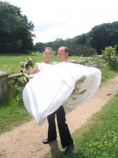Ženich přenáší nevěstu přes bahnitou cestu