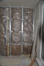 Strop po zaizolovaní a založený sadrokarton, stena zakrytá protiparovou zábranou.