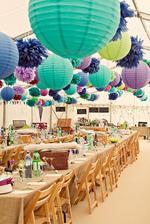 Kombinace lampionů a pom poms uvnitř svatebního stanu
