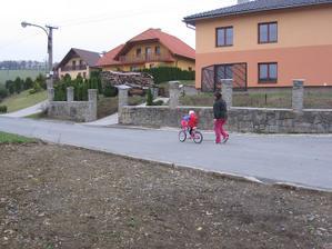 malá už jezdí sama na kole kolem domečku