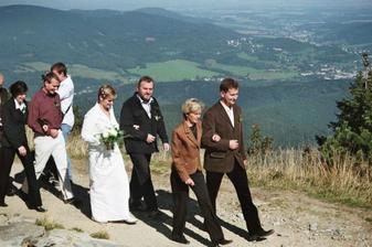 Svatební průvod vychází směrem ke zvoničce