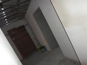 pohled z ložnice do chodby a do obýváku s kuchyní (za tou krabicí)
