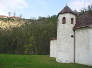 Skála, která se tyčín nad řekou protékající za tím stejným kostelíkem