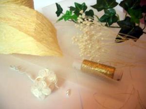 Potrebujeme... papierovu stuhu (kupene v kvetinarstve), zlatu nit, tyl, biele kvietky (3 kvietky na jednej stopke), zelene listky (brectan) a suchy kvet, z ktoreho sa daju trhat mensie casti a na zaver dve male perlicky.