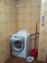 kout s pračkou po zboření regálu na ručníky...
