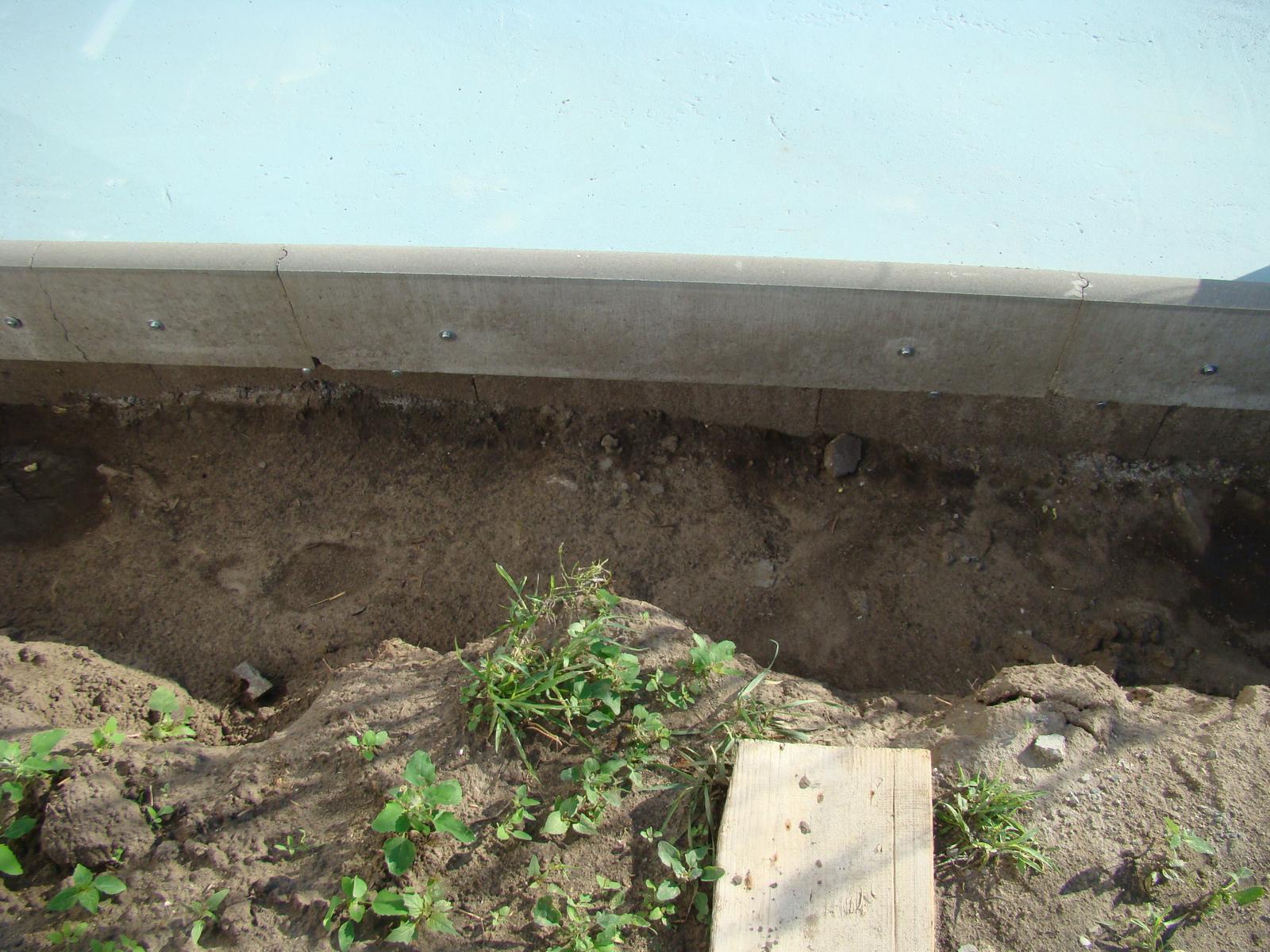 Terasa k domu - Na okraj betónovej plochy som upevnil do vymeranej výšky obrubníky.