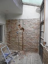 Tato zeď na verandě zůstane po výměně rozbitých cihel a zaspárování obnažená cihlová zeď.