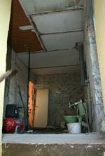 Pohled na koupelnu ze schodů. Na stropě je vidět původní rozvržení místností - odzadu: spíž, koupelna, WC, komora.