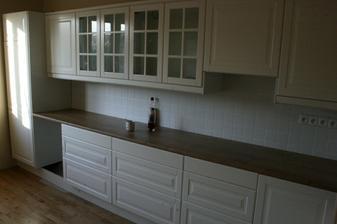 2.10.2012 - Pracovní deska usazena, horní skříňky visí, zasoklováno, krycí lišty a římsy nasazeny.