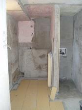pôvodný stav pohľadu na kúpelňu z chodby v procese rekonštukcie - nová dlažba