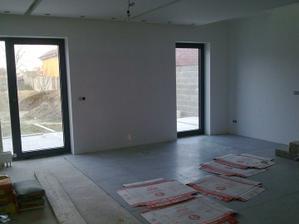 Štádium pokladania dlažby v obývačke, dlažba bude na celom dolnom podlaží jednotná.