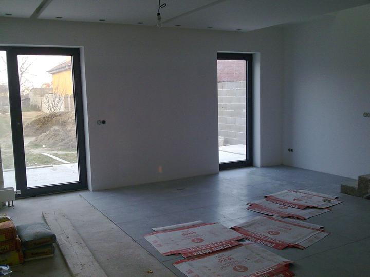 Príbeh našej stavby II - rok 2011 - Štádium pokladania dlažby v obývačke, dlažba bude na celom dolnom podlaží jednotná.