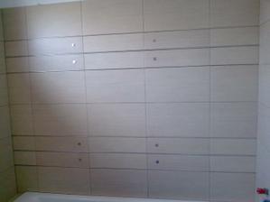 Obklad máme jednoduchý jednotnýv celej kúpelni, len nad vaňou si dekor obkladačky s tenkými nerezovými pásikmi a štvorčekmi