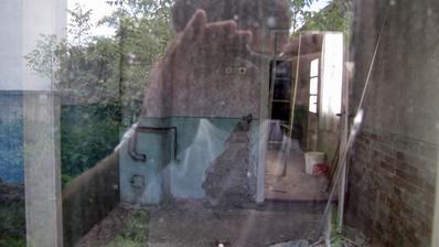 """Pohľad cez okno do interiéru ,zrejme budúcej """"kuchyňoobývačky""""."""