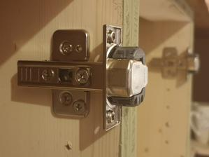 Závesy na dvere namontované. Zatiaľ iba na skrinky, kde budú obyčajne dvierka, nie rohové.