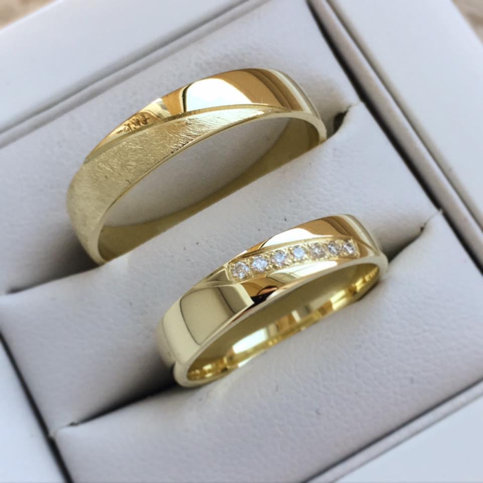 Exkluzívne obrúčky z našej dielne - Svadobné obrúčky zo žltého zlata. Na dámskom prsteni sa trblietajú jemné kamienky a pánsky model dotvára diamantový povrch.