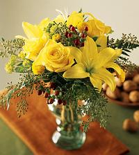 Sunny yellow lilies are combined with yellow roses, yellow button pompons and assorted greens.
